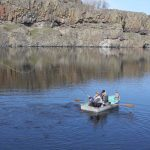 fishermen in small boat on lake