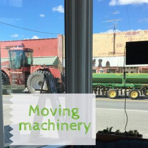Farm machinery moving down the street viewed through Harrington shop window
