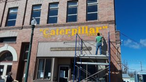 Gavin Wagner freshening up the Caterpillar sign on brick wall